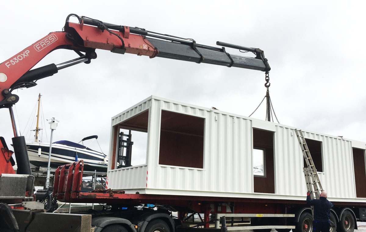Office container conversion being delivered by hiab